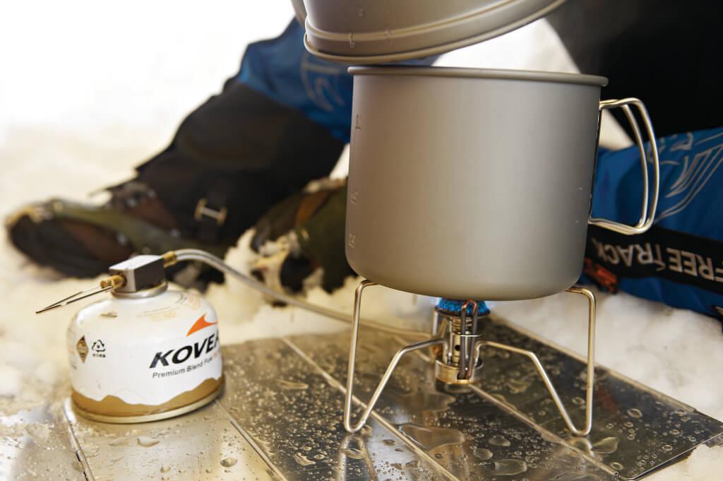 Kuchenka turystyczna Kovea - topienie śniegu by uzyskać wodę do picia