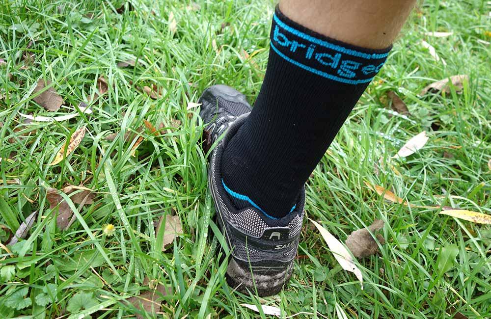Skarpety wodoszczelne Bridgedale StormSock w mokrej trawie.