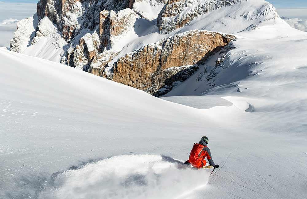 Narciarz skiturowy w puchu na tle gór.